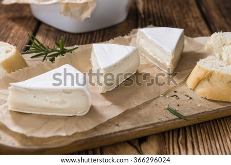 Pieces of Camembert on vintage wooden background (close-up shot)