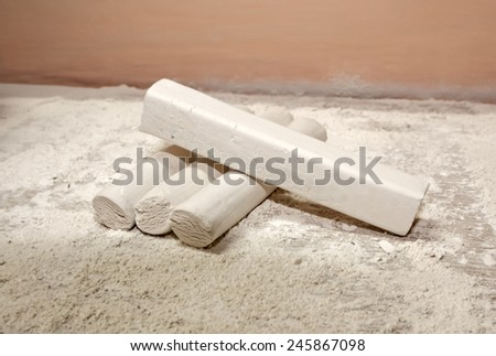 Pieces of chalk on a stand on the chalk dust - stock photo