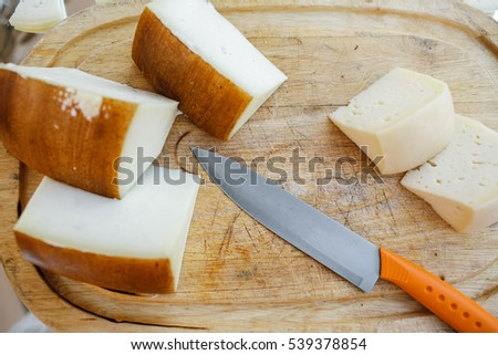 Pieces of cheese and knife with orange handle lie on wooden board