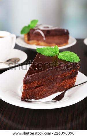 Pieces of chocolate cake on plates and cup of tea on wooden table on natural background - stock photo