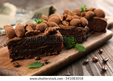 Pieces of chocolate cake with walnut and mint on the table, close-up
