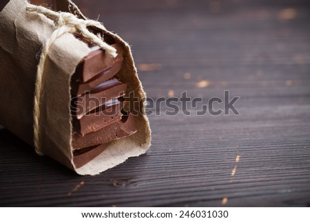 Pieces of chocolate packed in old styled paper, rustic style - stock photo