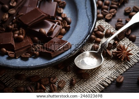 Pieces of chocolate with coffee beans, spices and silver teaspoon, rustic style - stock photo