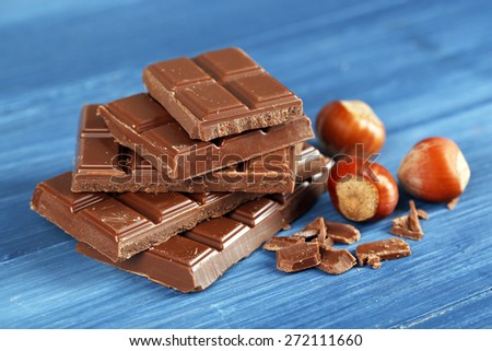 Pieces of chocolate with hazelnut on wooden table, closeup - stock photo