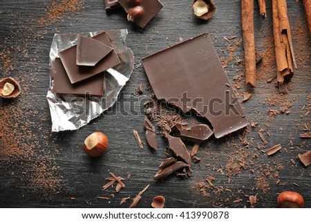 Pieces of chocolate with hazelnuts, cinnamon on black wooden background - stock photo