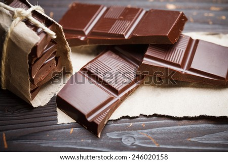 Pieces of chocolate with packing paper on wooden table, rustic style