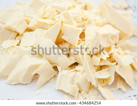Pieces of cocoa butter, white chocolate on white paper.