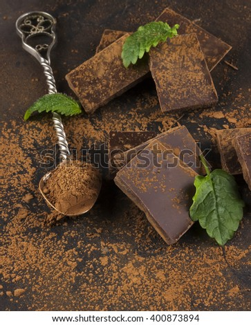 Pieces of dark chocolate, mint and cocoa powder - stock photo