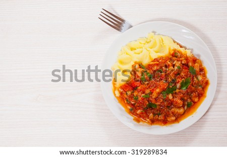 pieces of fish in tomato sauce with mashed potatoes - stock photo