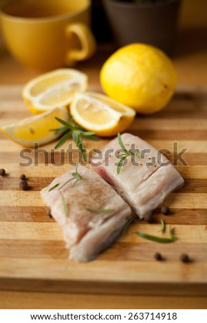 Pieces of fresh fish. Fish and lemon on a wooden desk with rosemary twig. Macro, fresh food, natural ingredients. Helpful on a diet. Healthy food. White fish fillets - stock photo