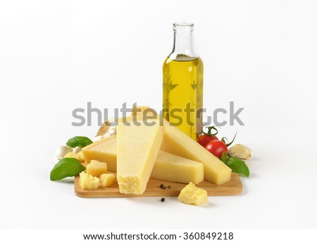 pieces of fresh parmesan cheese, vegetable garnish and bottle of olive oil on white background - stock photo