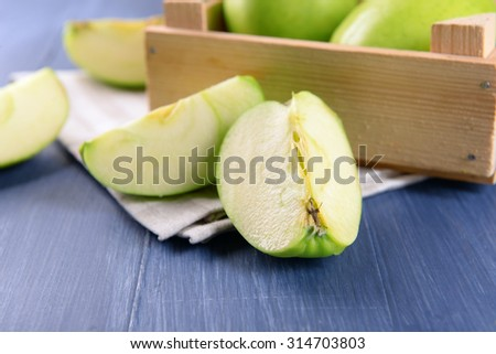 Pieces of green apple on wooden table, closeup