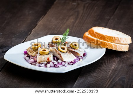 pieces of herring in oil on chopped onion - stock photo