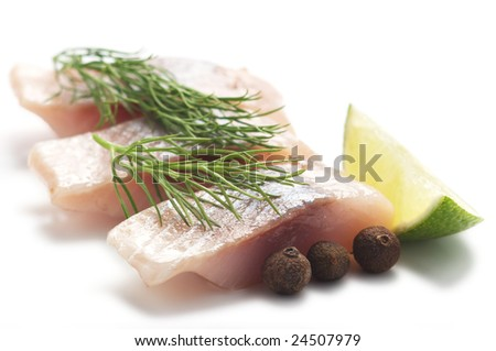 Pieces of herring with lime, pepper and dill isolated on a white background.
