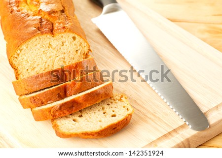 Pieces of homemade banana bread with a knife and a cutting board. - stock photo