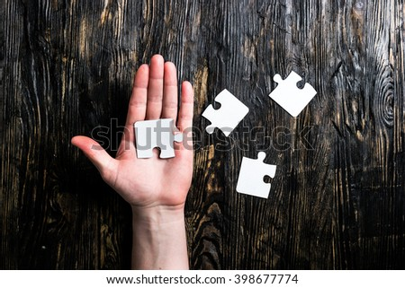 pieces of jigsaw on table and on palm - stock photo