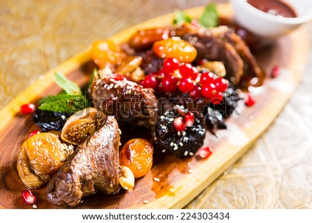pieces of lamb cooked on the grill. served with fruit