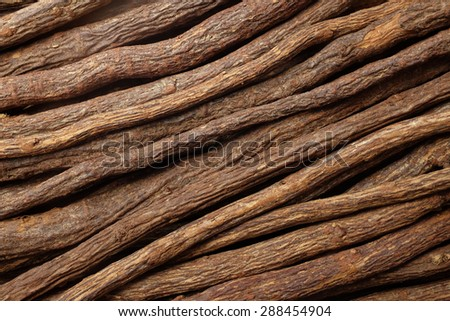 Pieces of liquorice root piled diagonally as an abstract background texture - stock photo