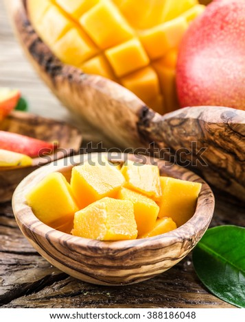 Pieces of mango fruit in the wooden bowl.