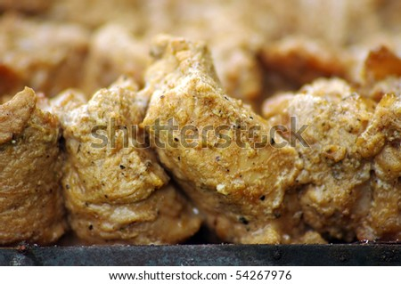Pieces of marinated pork on barbecue