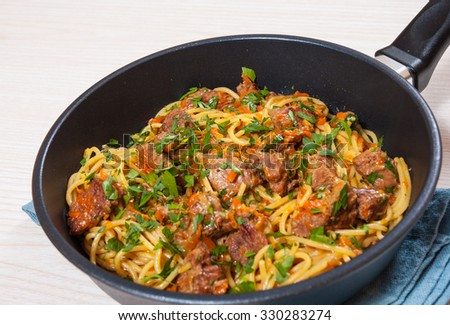 pieces of meat and vegetables with spaghetti in a frying pan