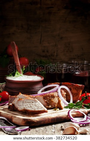Pieces of meat barbecue on a wooden cutting board with vegetables, spices, herbs, sauce and wine, selective focus