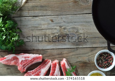 pieces of meat for steaks, parsley and dill, with a mixture of pepper and olive oil, a frying pan, in a frame, top view, - stock photo