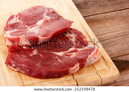 pieces of meat on a wooden cutting board