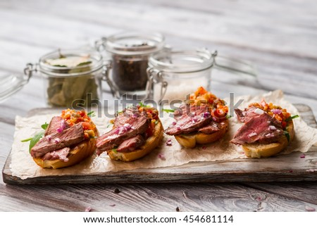 Pieces of meat on toasts. Mixture of chopped vegetables. Recipe of bruschetta with veal. Meal that's easy to cook. - stock photo