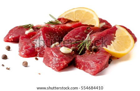 Pieces of meat with garlic, lemon and rosemary on wooden board isolated. Raw beef.
