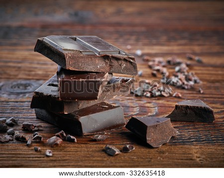 Pieces of natural dark chocolate on wooden table - stock photo
