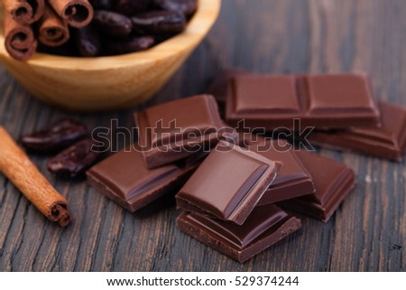 Pieces of natural dark chocolate on wooden table