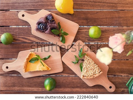 Pieces of nut cake, brownie and cheesecake decorated with mint, lemon and lime on wooden table. top view - stock photo