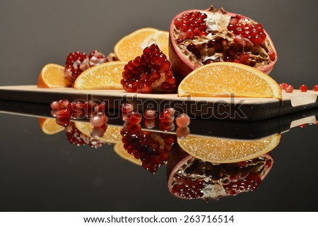 Pieces of pomegranate and orange wedges on a wooden Board