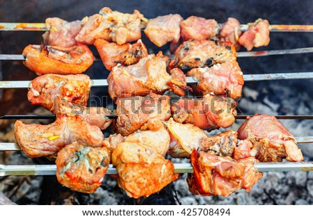 Pieces of pork being roasted on skewers over charcoal