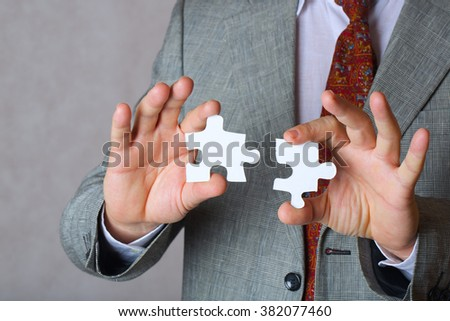 Pieces of puzzle in the hands of a business man. Closeup. Free space for a text