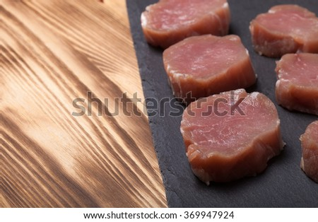 Pieces of raw meat on a plate of slate on a new burned wooden background. Selective focus. - stock photo