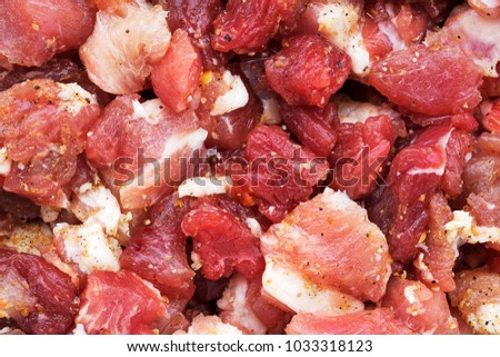 Pieces of raw meat, pork and beef, with spices.  View from above.