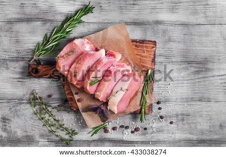 Pieces of raw pork steak with spices and herbs rosemary, thyme, basil, salt and pepper on a bright white wooden background in rustic style, top view - stock photo