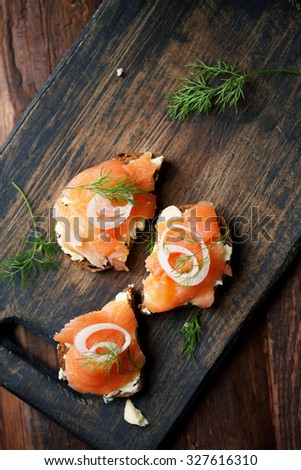 Pieces of red fish and butter on rye bread - stock photo