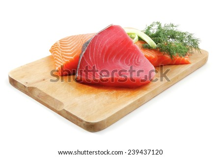 pieces of salmon and tuna fish on wooden plate isolated on white background