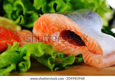 pieces of  salmon with spice on wooden plate