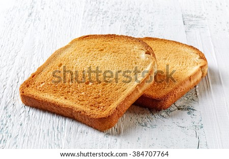 Pieces of sliced toast bread on white wooden table - stock photo