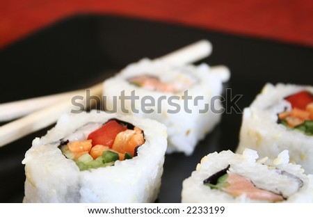 Pieces of  sushi on a black plate.  Very shallow D.O.F.- Only piece in the foreground are in focus. - stock photo