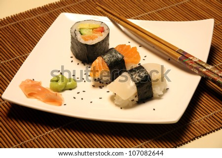 pieces of sushi on square plate - stock photo