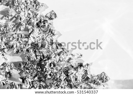 Pieces of torn crumpled silver foil laid symmetrical pattern on white background. Sunlight with reflected light and shadows. Space for text.