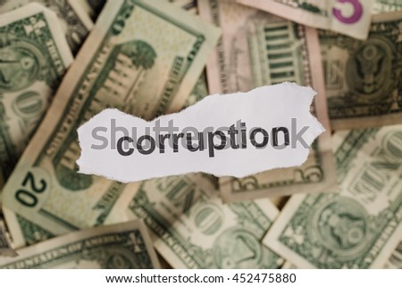 Pieces of torn white paper with CORRUPTION word on money blur background. design and business concept.