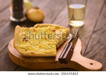 Pieces of traditional German Zwiebelkuchen (onion cake), made of yeast dough, onions and bacon in cream sauce, with cutlery on wooden board (Selective Focus, Focus in the middle of the first piece)