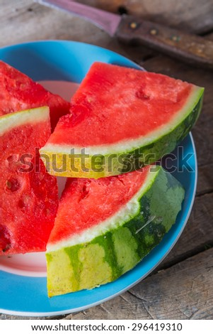 Pieces of watermelon on a plate on a wooden table - stock photo
