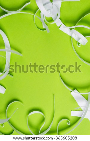 Pieces of white torn paper over the green background - stock photo